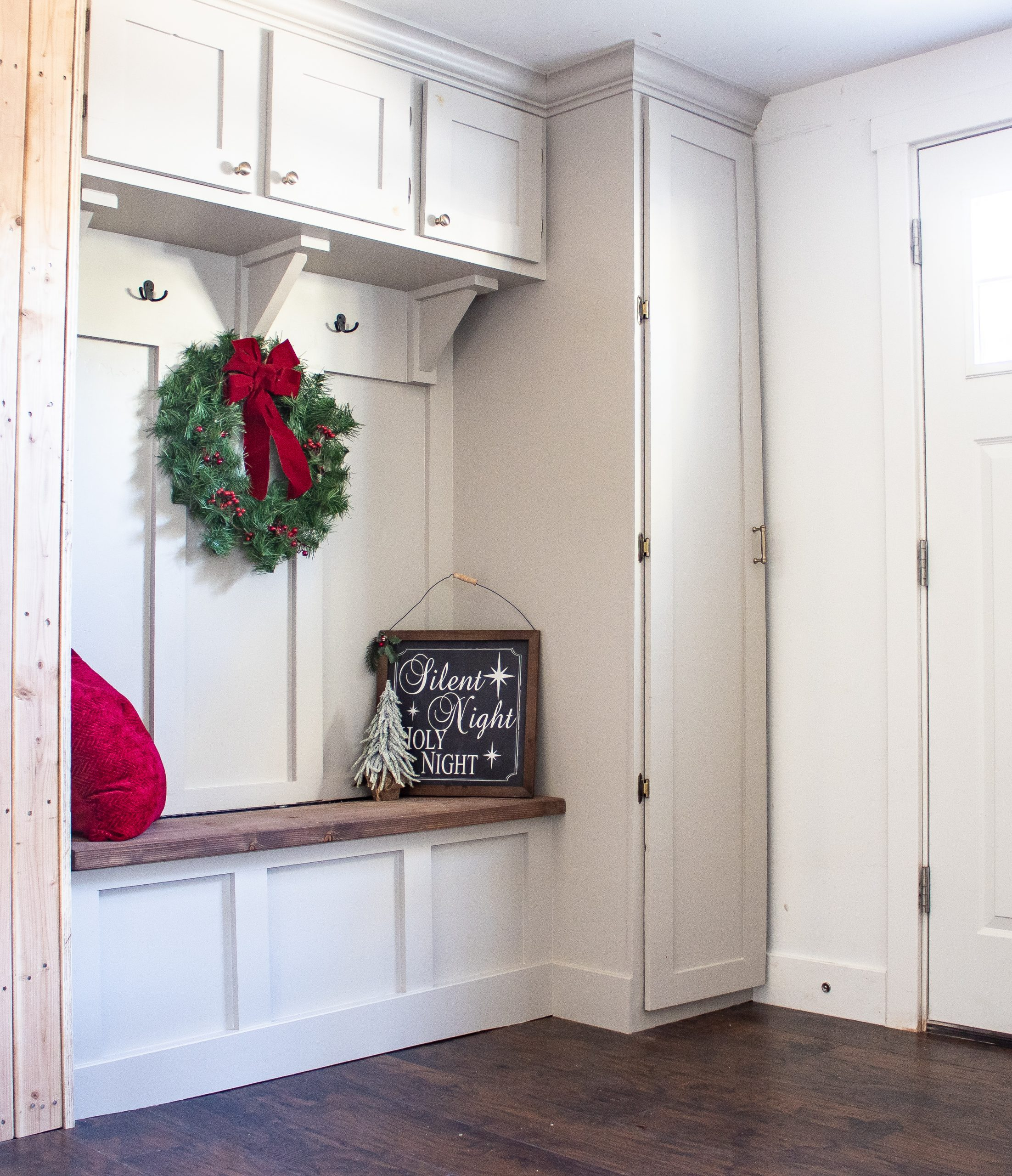 Gray mudroom with storage bench and coat closet decorated for Christmas